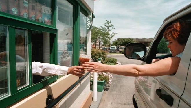 A driver reaches for her coffee order through a window at a drive-up Starbucks Coffee shop June 23, 2000 in Lombard, IL. Legislators in New Jersey want to pass a distracted driving law that would prohibit drinking, eating and other activities while driving.