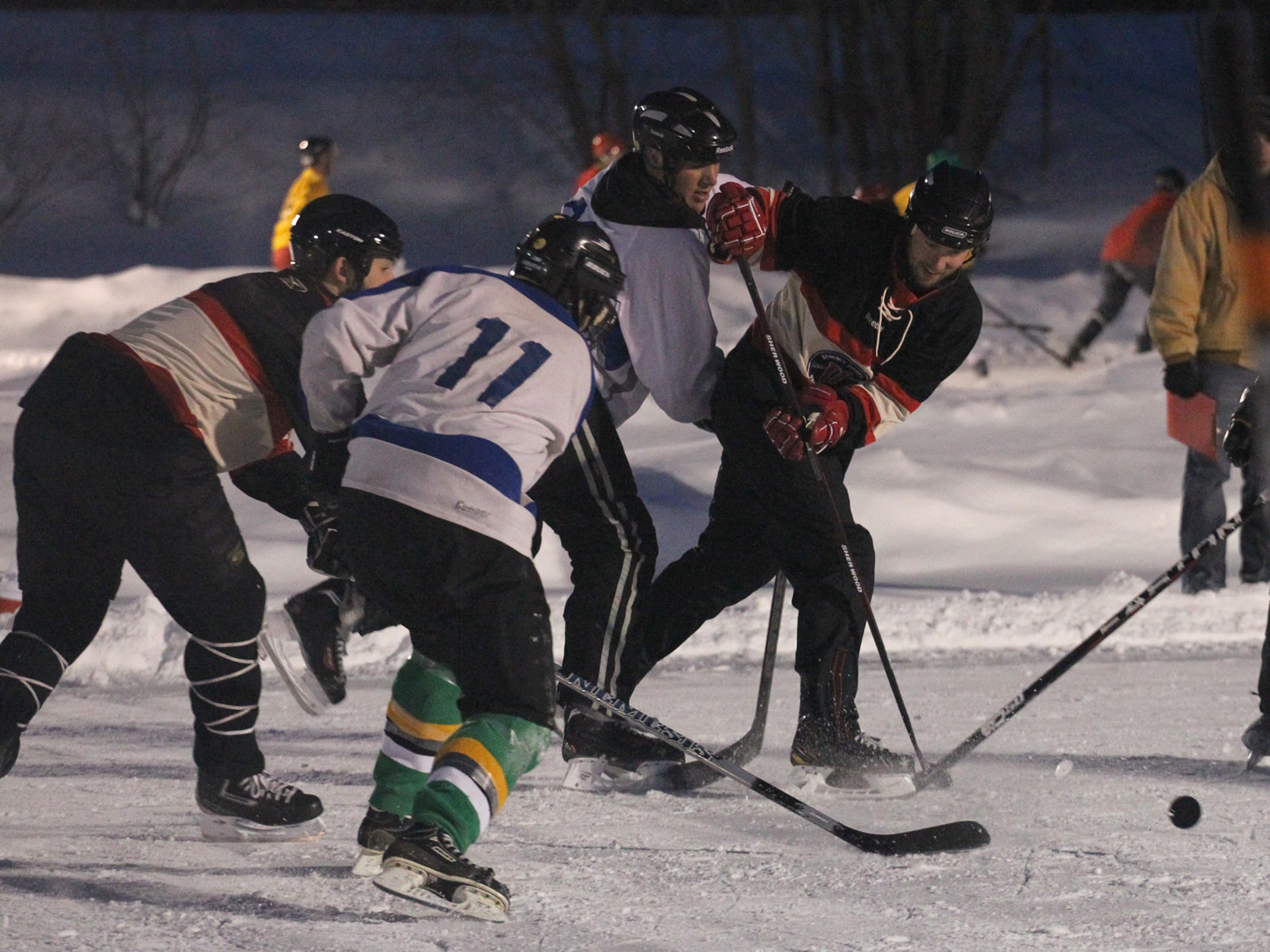 In this 2013 file photo, players battle for the puck at the Midwest Freeze Leinenkugel's Classic Adult Pond Hockey tournament Friday at Sunny Vale Park in Wausau.