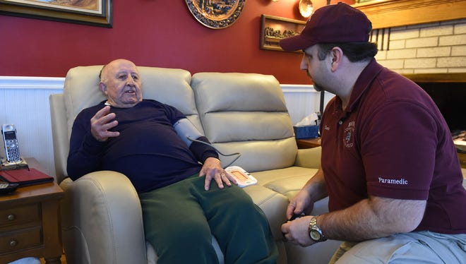David Sator, a community paramedic with Baxter Regional Medical Center, checks on patient Charley Angel, 81, at his Bull Shoals home. BRMC's pilot Community Paramedic Program is about to become available statewide following a unanimous vote of the Arkansas Legislature.