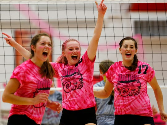 East's Becca Young(15), left, Ally Geurink(10), and Naomi Murphy(17), celebrate a point Thursday night during 'The Pink Game' for cancer awareness volleyball match against West at Wausau East High School.