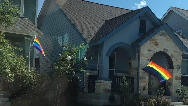 Pride flags adorn neighboring houses in the Goodnight Ranch neighborhood in Southeast Austin. Residents have been hanging the flags in a show of solidarity for neighbors whose flag was stolen two weeks ago.