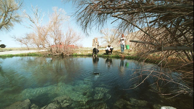 Dawn Schoennauer, left, Doug Cook, center, and Dan Pablo relax at the edge of Frog Pond Hot Spring at the Black Rock Desert in Nevada March 27, 1999.