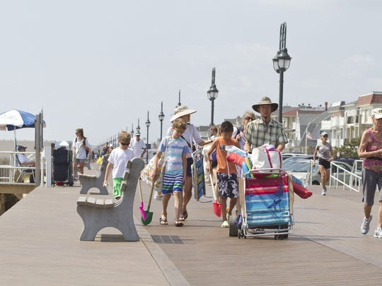 The state reported Thursday that the Jersey Shore – particularly Monmouth and Ocean counties – saw a pickup in tourism spending in 2014. Beachgoers walk along the Belmar boardwalk in this 2014 file photo.