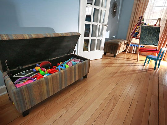 Toys are neatly stored in unique functional bench chests on one side of the living room.