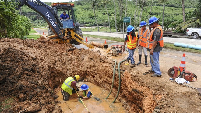 Guam Waterworks Authority employees in a hole measure the length for a replacement pipe needed to repair a 12-inch line water break under the roadway at Talofofo Bay on Monday, Aug. 17.