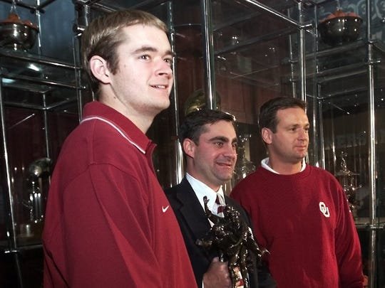 Oklahoma quarterback Josh Heupel, left, and coach Bob Stoops, right, pose with Bernad Pellegrino, President of the Walter Camp football foundation, center, after Heupel was presented with the foundation's player of the year award Tuesday, Nov. 28,2000 before Stoops's weekly press conference in Norman. The foundation named Stoop coach of the year. The Associated Press named Stoops as Big 12 Coach of the Year today.