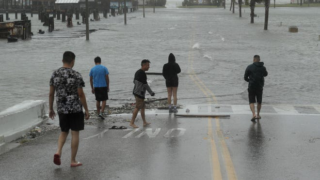 Onlookers gather on a road beginning to flood as Hurricane Hanna makes landfall, Saturday, July 25, 2020, in Corpus Christi, Texas.