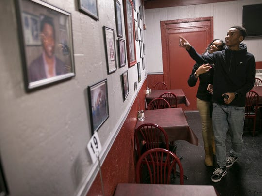 Shakayla Keyes (left) and Deadrick Taylor, both of Indianapolis, take a look at the celebrity photos on the wall at Kountry Kitchen, a soul-food restaurant in the Kennedy-King neighborhood.