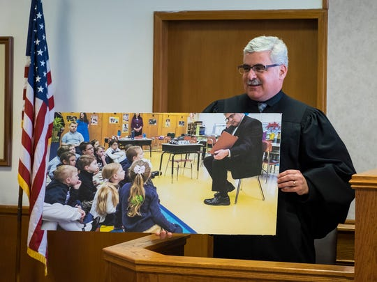 St. Clair County Probate Judge John Tomlinson holds a printed photo of him reading to a classroom at  Holy Cross Catholic School before the Mental Health Court graduation Tuesday, April 17. The photo was a gift to Judge Tomlinson from Supreme Court Justice Kurtis Wilder.