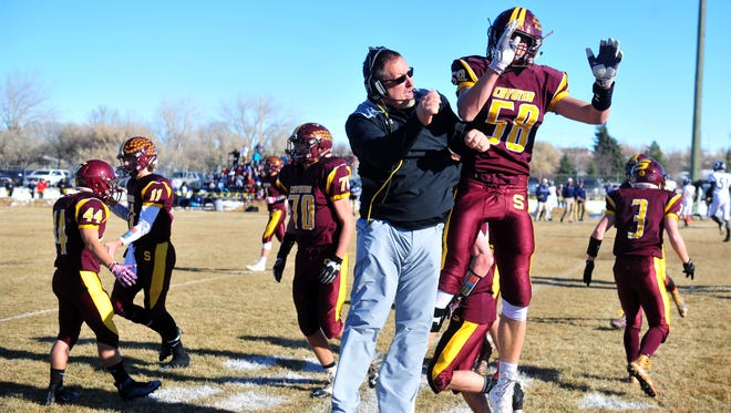 Shelby head football coach Mike White celebrates with lineman TJ Reynolds during the Coyotes' Class B semifinal game against Missoula Loyola in November. Shelby will compete in Eight-Man football next season.