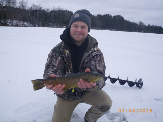 """Tyler Nikkila with a 17"""" brown from a managed trout"""