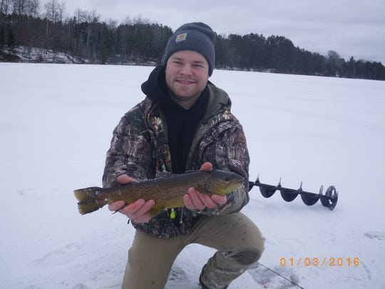"Tyler Nikkila with a 17"" brown from a managed trout lake near the Upper Chippewa Basin"