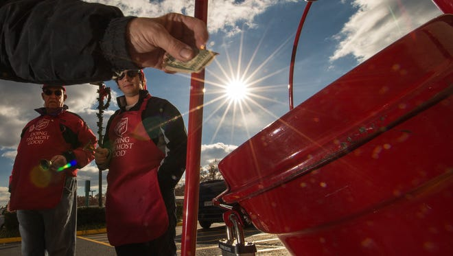 Salvation Army volunteers ring their bells watching a donation drop into a kettle outside a Giant grocery store Nov. 24, 2012, in Clifton, Va.