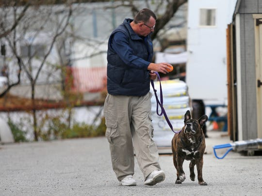 Pete Buchmann plays his 9 year-old dog Buster while taking him for a daily walk at Faithful Friends.
