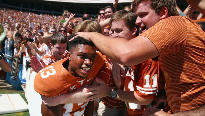 Jerrod Heard #13 of the Texas Longhorns celebrates with fans after beating the Oklahoma Sooners 24-17 during the AT&T Red River Showdown at the Cotton Bowl on October 10, 2015 in Dallas, Texas.