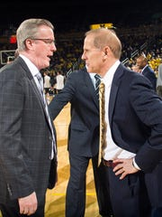 Iowa coach Fran McCaffery, left, talks with Michigan coach John Beilein.