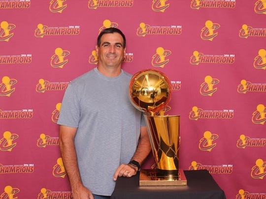 Fort Myers' Dan Mills, a Cleveland Cavaliers season-ticket holder, poses with the Larry O'Brien trophy.
