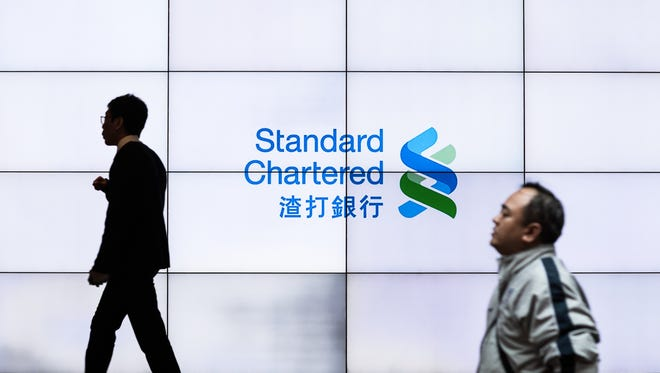 A man walks past an electronic board screen in a branch of the Standard Chartered bank in Hong Kong.