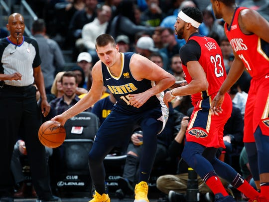 Denver Nuggets center Nikola Jokic, left, of Serbia, works the ball inside for a shot as New Orleans Pelicans forward Anthony Davis defends in the first half of an NBA basketball game Friday, Dec. 15, 2017, in Denver. (AP Photo/David Zalubowski)