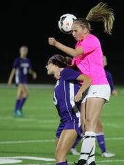 South Kitsap soccer player Savannah Foster jumps high for a header over Sumner's Maria Rink in a game against Sumner.