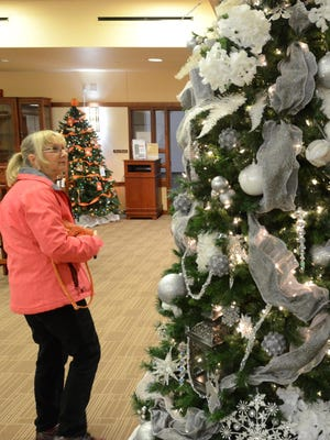 Nancy Bourgeois checks out some of the decorated efforts at the Northville Community Center's Festival of Trees. Organizations from Northville and Northville Township have decorated Christmas trees that will be on display at the center through the holiday season.