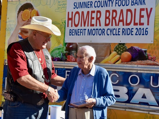 Sumner County Food Bank Executive Director James Gill, left, recognized Fall Ride for Food organizer Homer Bradley as the nonprofit's lifetime ambassador Oct. 8.
