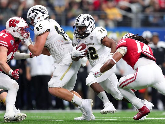 Western Michigan's Jamauri Bogan is tackled by D'Cota Dixon (14) of the Wisconsin Badgers in the second quarter of the 81st Goodyear Cotton Bowl Classic at AT&T Stadium on Jan. 2, 2017 in Arlington, Texas.
