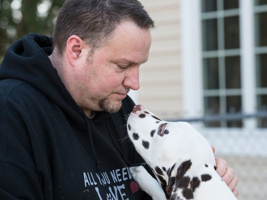 Randy Creasy holds his dog, Chance, at the Animal Wellness
