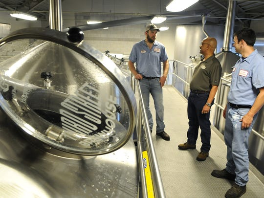 Brewer Karl Schmitz, (left to right) Horace Cunningham, director of brewing, and brewer Bob McKenzie watch May 31 as a batch of mash transfers at the Third Street Brewery in Cold Spring.