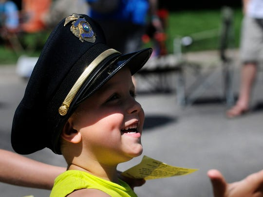 A police officer's son jokes around with another officer on the sidelines of the Sartell SummerFest Parade in 2018.