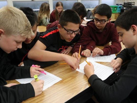 Parsons Junior High School students Micah Graham, 12, from left, Taylor Manivon, 12, Beto Zapien, 13, Angel Cervantes, 12, Gabriel Nunez De La Torre, 12, and Alex Buchko, 12, highlight points of the president's inaugural speech to discuss Friday at the school in Redding.