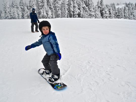Kale Louderback, 4, tries snowboarding for the first time with his dad, Mickey, at Hurricane Ridge.