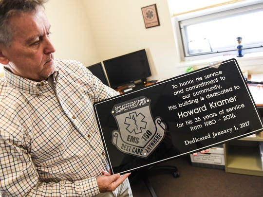 Howard Kramer poses with a commemorative sign thanking him for his 36 years of service, dated Jan. 1, 2017. It will hang inside the vestibule of that tower-like structure inside the main entrance.