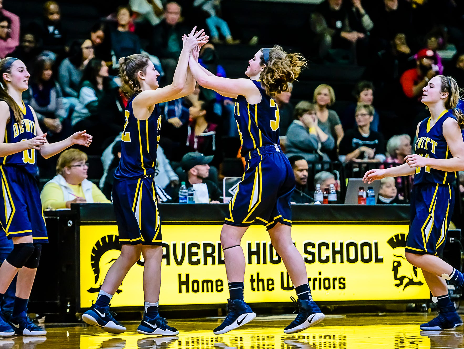 Grace George ,second from right, high-fuves teammate Piper Phillpis ,second from left, after their win over Waverly Friday February 10, 2017 in Delta Township. KEVIN W. FOWLER PHOTO