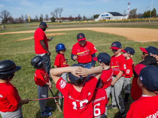 Manager Joe Luongo gathers players together before the start of a game between New Castle Little League's minor baseball Indians and Cardinals teams on Opening Day in 2014.