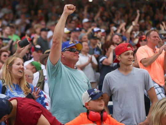 Fans react as IndyCar driver Takuma Sato crosses the
