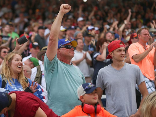 Fans react as IndyCar driver Takuma Sato crosses the finish line two-tenths of a second before driver Helio Castroneves, winning the 101st running of the Indianapolis 500 at Indianapolis Motor Speedway, Sunday, May 28, 2017.