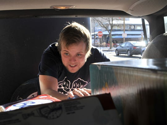Justin Michael, who is organizing the Central Minnesota Common Roots Festival, is also involved with other community initiatives. Picture here, he  closes the hatch on a trunk full of diapers collected in 2015 to distribute to local nonprofits.