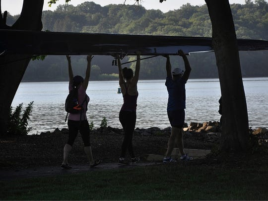 Cortlandt rowers are silhouetted against the backdrop