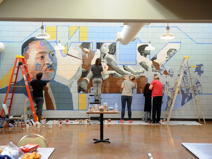 Volunteers work on the Martin Luther King mural Saturday,