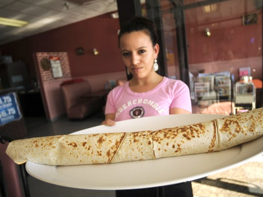 A server at El Rey Burritos in West Des Moines delivers the Rey Rey, a burrito spanning more than two feet with three types of meat, to staff writer Joe Lawler's table. Lawler was able to eat the whole burrito in about an hour.  Eric Rowley/Juice photos