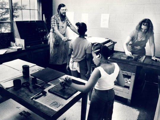 Nathalie Andrews, right in back, and Gray Zeitz show Michelle Ellery, 7, white top, and Jessica Gain, 9, how to operate the Portland Museum's old printing press in 1983.