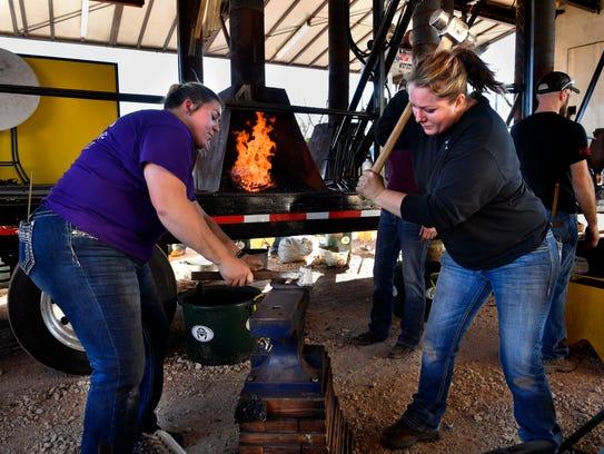 Ashlee Dinges holds her horseshoe as Nikki Smith strikes
