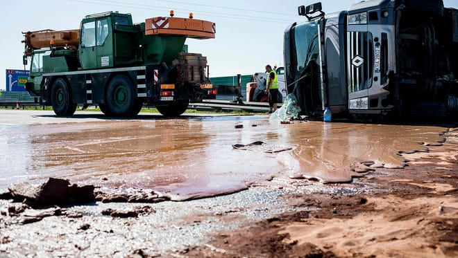 Tons of spilled liquid milk chocolate block six lanes on a highway after a truck transporting it overturned near Slupca, in western Poland on Wednesday.