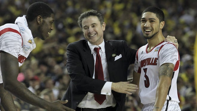 U of L head coach Rick Pitino, center, congratulates Peyton Siva, #3, right, during the closing seconds of their win over Michigan during the NCAA Championship game.  Montrezl Harrell, #24, was at left. Apr. 8, 2013
