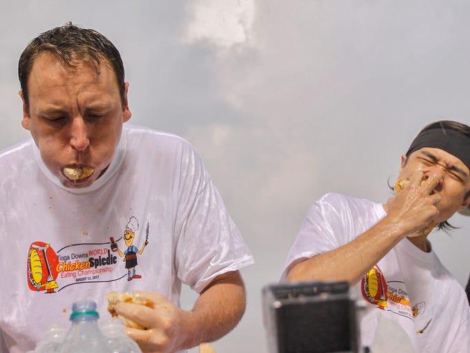 Heavy rain soaks contestants while Joey Chestnut, left,