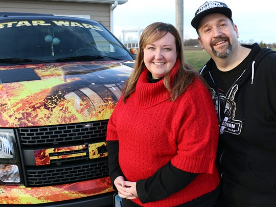 """Diehard """"Star Wars"""" fans Nancy and Trey Laymon pose in front of their custom decorated pickup that not only has Darth Vader's face on the hood -- it also can blare the sound of Vader's breathing or Chewbacca's growl."""