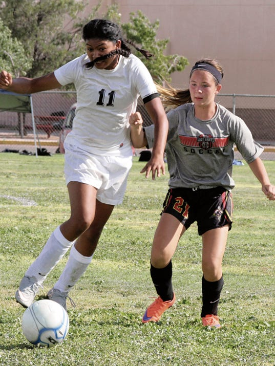 """Bill Armendariz - Headlight Photo   Lady Cat Alyssa """"Cheeks"""" Magana (11) works to get a free ball past a Centennial High midfielder during Saturday's round-robin scrimmage session at the Deming High Soccer Field."""