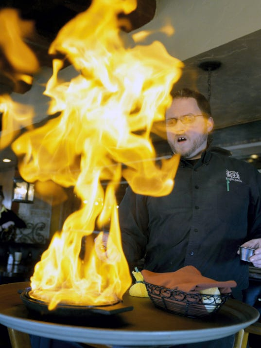 Eagles Nest server Wayne Miller flambés a saganaki appetizer of kefalograviera cheese table-side in the restaurant on Saturday, April 4, 2015, in Springettsbury Township. The restaurant was built in 1937, and has been under its current management since 2008. Chris Dunn — Daily Record/Sunday News
