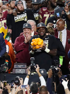 Florida State Seminoles running back Dalvin Cook (center with oranges) reacts after being named the most valuable player of the game against the Michigan Wolverines at Hard Rock Stadium. The Seminoles won 33-32.